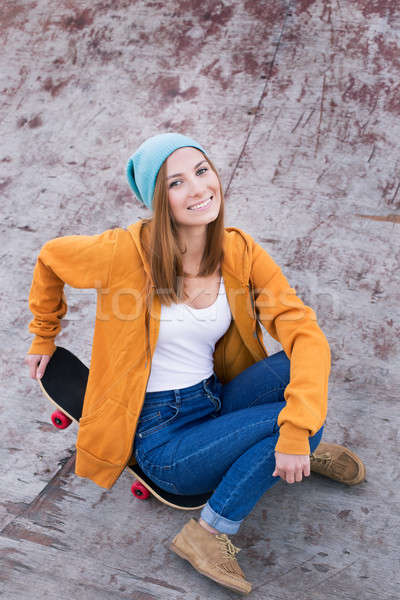 Student sitting on skateboard and smiling at the camera Stock photo © Agatalina