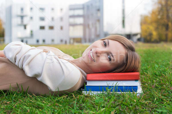 Student lying on green grass and books Stock photo © Agatalina