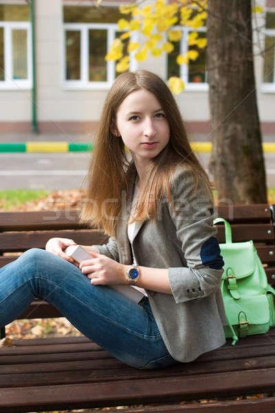 студент сидят скамейке книга глядя камеры Сток-фото © Agatalina
