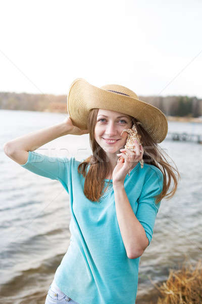 Freckled girl listening seashell Stock photo © Agatalina