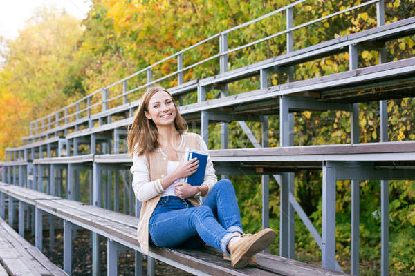 Student sitting on sport tribune with book Stock photo © Agatalina
