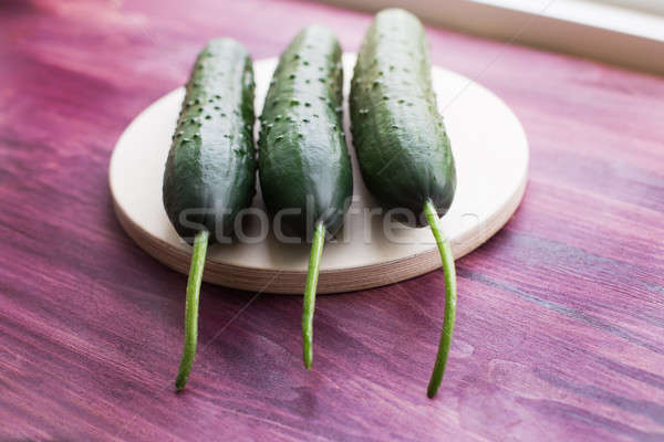 Three fresh cucumbers lying on windowsill Stock photo © Agatalina