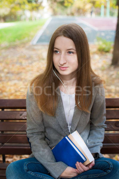 Student sitting on bench with headphones and book Stock photo © Agatalina