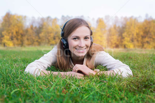 Student listening to headphones and lying on green grass Stock photo © Agatalina