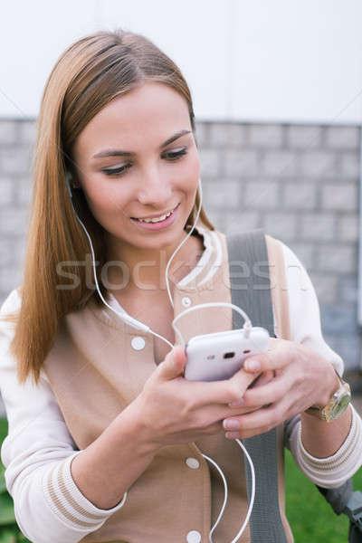 студент глядя телефон улыбаясь мобильных портрет Сток-фото © Agatalina
