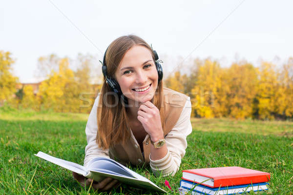 Student listening to headphones and reading book Stock photo © Agatalina