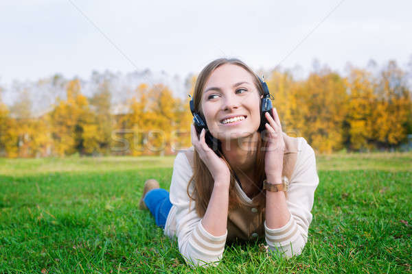 Student listening to headphones and looking towards Stock photo © Agatalina