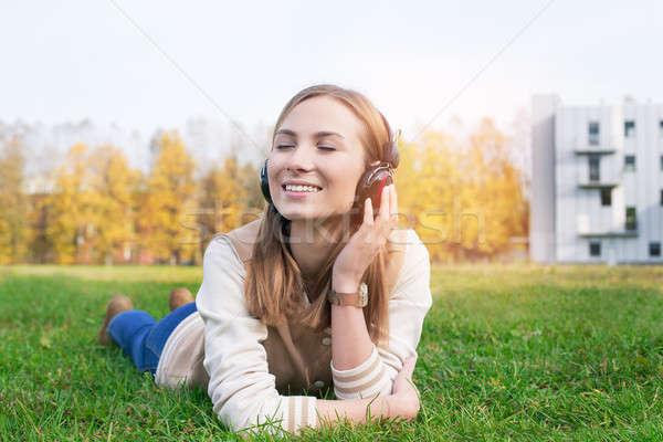 Estudante grama escuta música fones de ouvido grama verde Foto stock © Agatalina