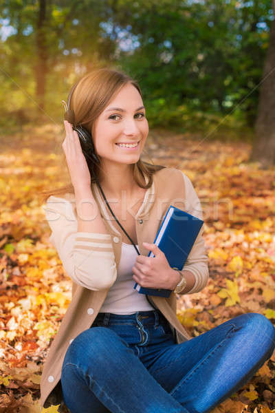 Student sitting among maple leaves, listening to headphones and  Stock photo © Agatalina