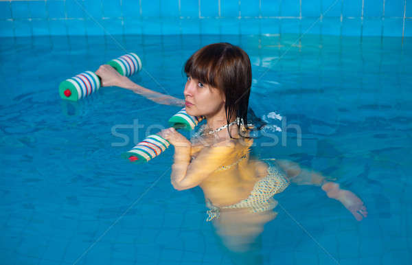 Attractive girl trains in aqua aerobics Stock photo © Aikon
