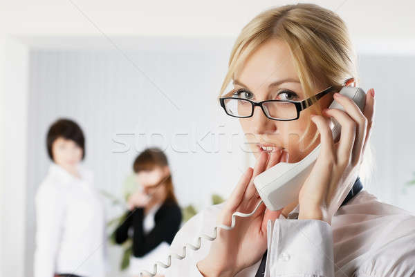 Attractive woman calls by wire phone in office Stock photo © Aikon