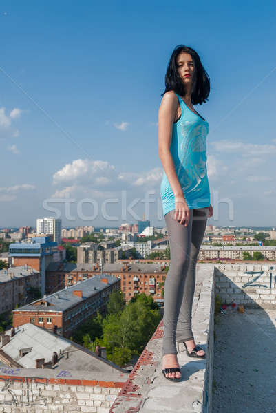 Attractive serious woman stands on building roofroof Stock photo © Aikon