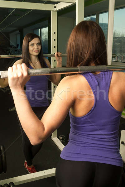 Woman doing shoulder exercise with weight bar Stock photo © Aikon