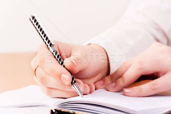 Woman writing in organizer Stock photo © Aikon