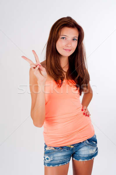 Attractive girl with freckles shows victory sign Stock photo © Aikon