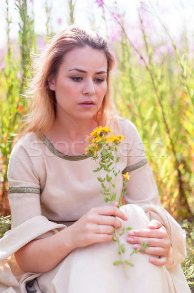 Beautiful sad girl sitting on meadow Stock photo © Aikon