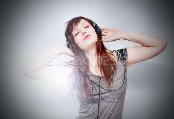 Beautiful young woman listening to music with headphones on neutral background Stock photo © Ainat
