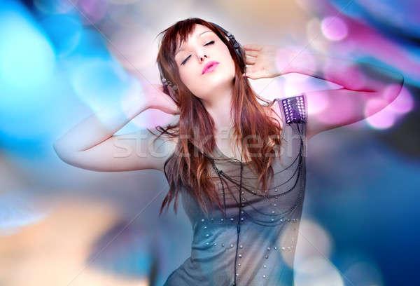Gyönyörű fiatal nő zenét hallgat fejhallgató színpad fények Stock fotó © Ainat