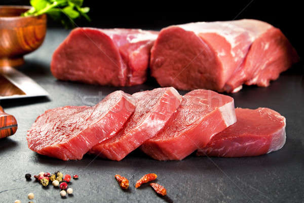 Fresh and raw meat. Sirloin medallions steaks in a row ready to cook. Background black blackboard Stock photo © Ainat