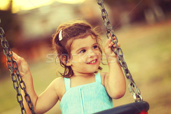 Little girl laughing and swinging on a swing Stock photo © ajfilgud