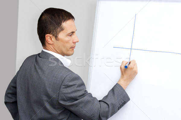 Businessman drawing on whiteboard Stock photo © ajfilgud