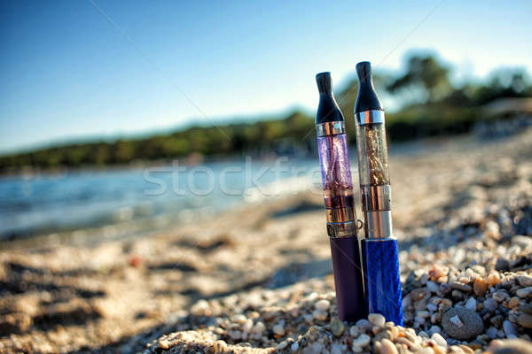 Stock photo: Two Electronic Cigarettes stuck in sand