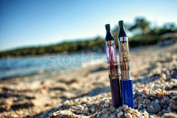 Two Electronic Cigarettes stuck in sand Stock photo © ajfilgud