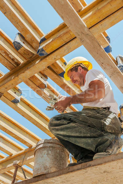 Smiling construction worker busy under slab formwork beams Stock photo © akarelias