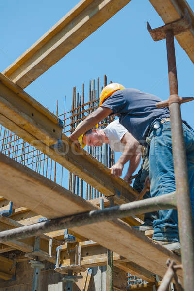 Construction workers placing formwork beams Stock photo © akarelias