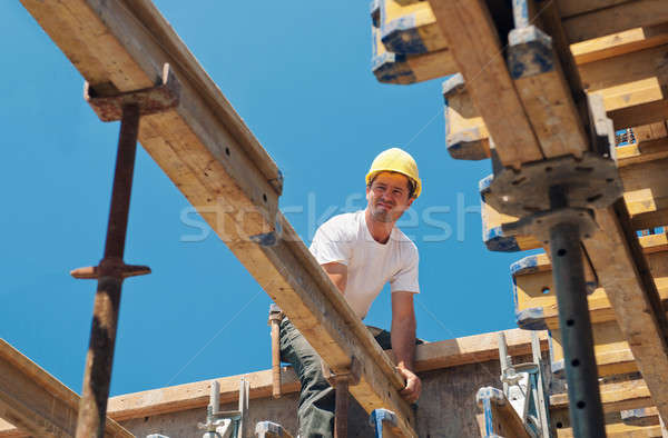 Construction worker placing formwork beams Stock photo © akarelias