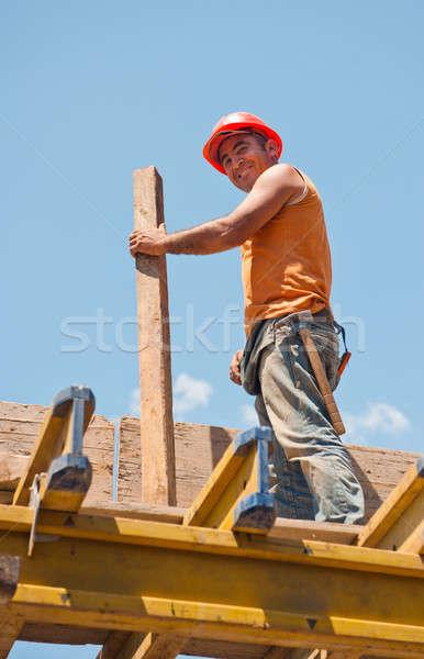 Smiling construction worker with formwork beam  Stock photo © akarelias