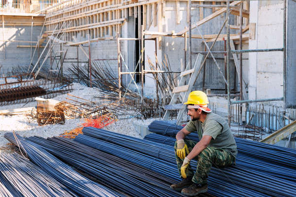 Construction worker resting on steel bars Stock photo © akarelias