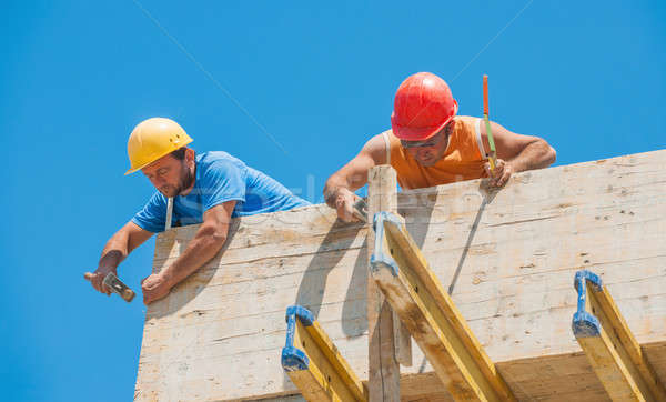Construction workers nailing cement formwork in place Stock photo © akarelias