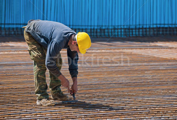 Construction worker installing binding wires Stock photo © akarelias