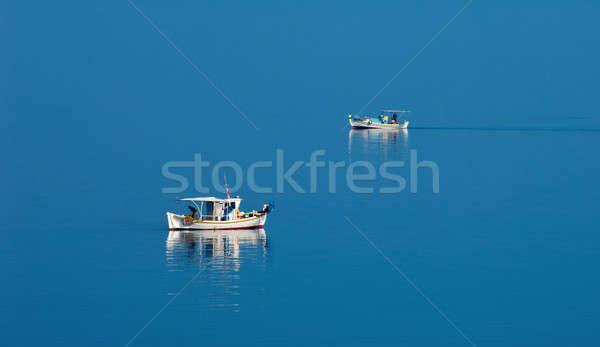 Two fishing boats in serene scene Stock photo © akarelias