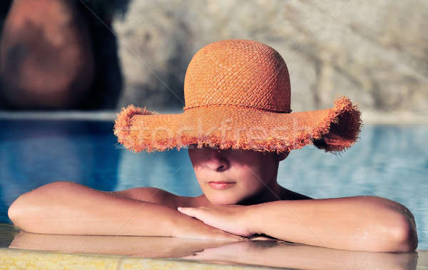 Attractive young woman in hat resting by the side of a pool Stock photo © akarelias