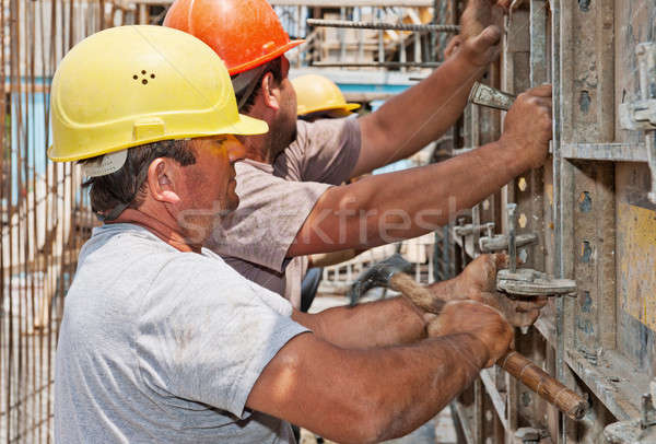 Construction workers positioning cement formwork frames Stock photo © akarelias