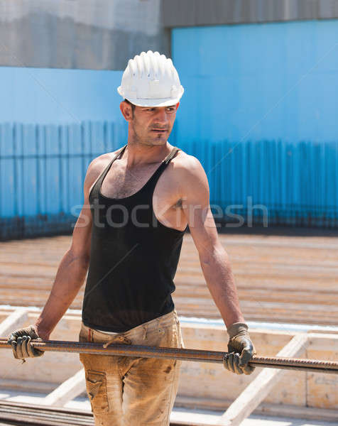Construction worker carrying reinforcement steel bars Stock photo © akarelias