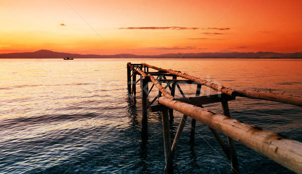 A wooden unfinished wharf against a red sunset Stock photo © akarelias