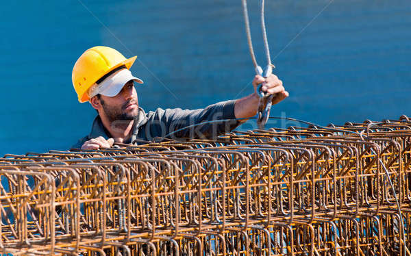 Construction worker loading stack of reinforcement beam cages to Stock photo © akarelias