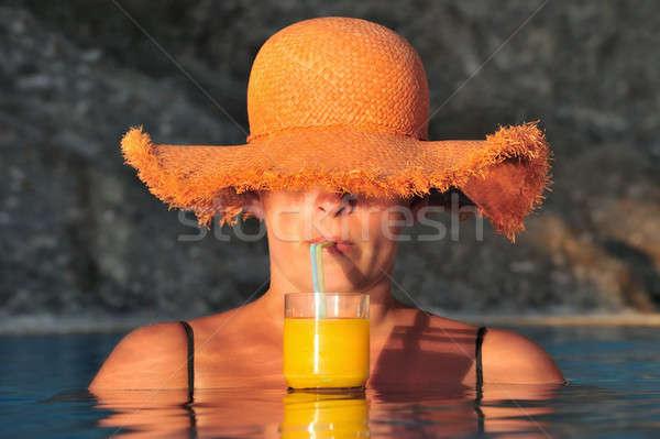 Atraente mulher jovem legal beber piscina chapéu de palha Foto stock © akarelias