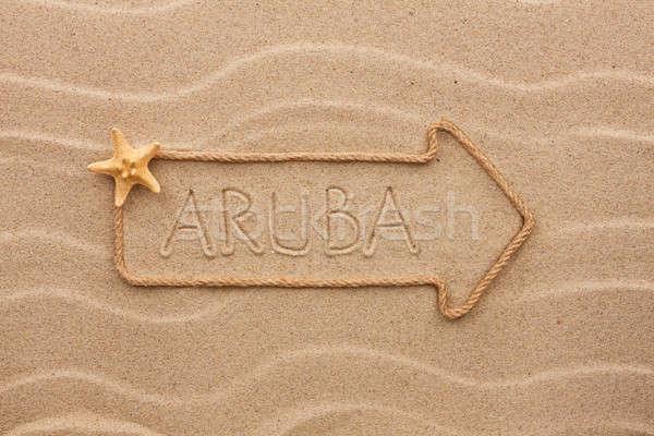Arrow made of rope and sea shells with the word Aruba on the san Stock photo © alekleks