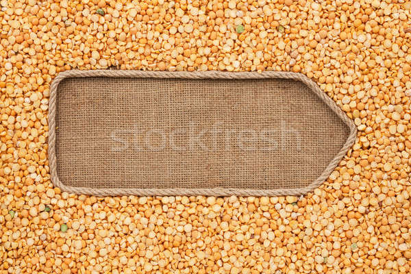 Stock photo: Pointer made from rope with grain peas  lying on sackcloth