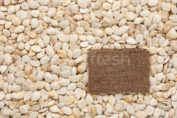 Tag made of burlap lies against the backdrop of pumpkin seeds Stock photo © alekleks