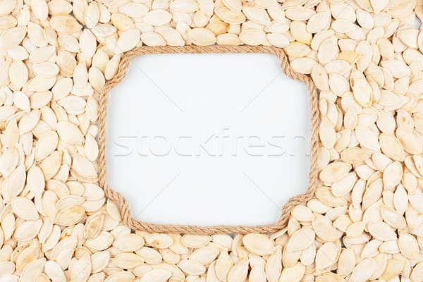 Figured frame made of rope with  pumpkin seeds  lying on a white Stock photo © alekleks