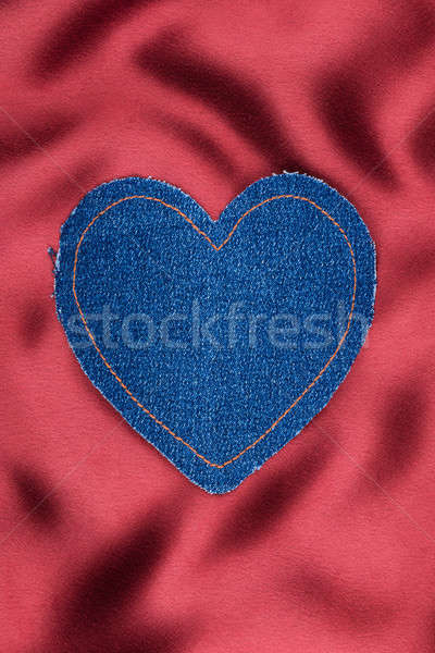 Heart made of denim fabric with yellow stitching on red silk Stock photo © alekleks