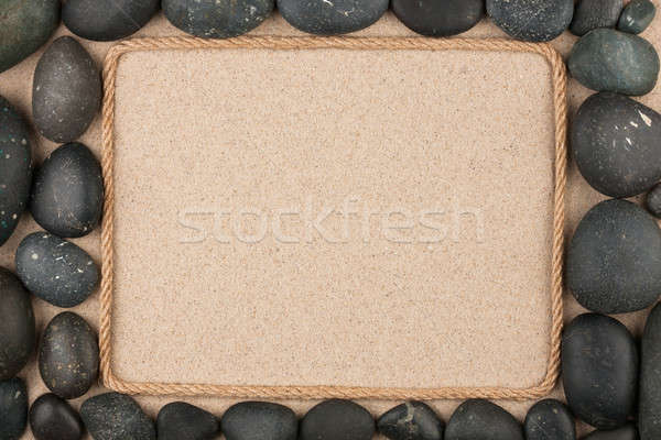 Frame made of rope lying on the sand among the black stones Stock photo © alekleks
