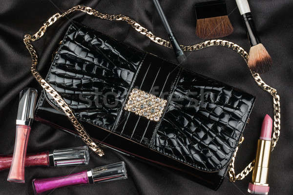 Beautiful bag from patent leather and cosmetics lying on black s Stock photo © alekleks