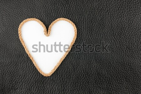Symbolic heart made of rope lying on a natural leather  Stock photo © alekleks