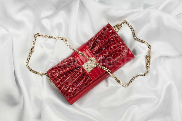 Stock photo: Red lacquer bag lying on a white silk